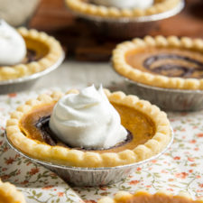 Close up of tarts on a table with a pumpkin base and topped with whipped cream