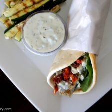 A wrapped Grilled Chicken Souvlaki Pita on a plate next to a small bowl of dipping sauce and grilled zucchini strips