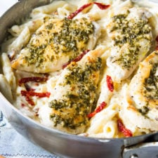 A pan of chicken and noodles in a white sauce with sun dried tomatoes slices