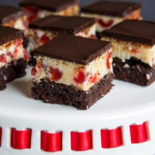 Close up of brownie squares on a plate, with a white chocolate fudge with cherries layer and a chocolate topping