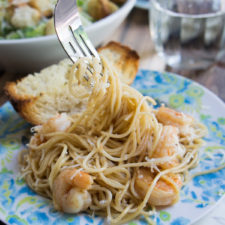 A plate with Garlic and Brown Butter Shrimp Pasta and a slice of bread
