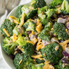 A bowl of food with broccoli salad, topped with cheese