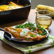 A plate of food on a table, with an enchilada and a salad