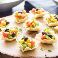Individual mini taco shells displayed on a table, with guacamole, corn, beans and tomatoes