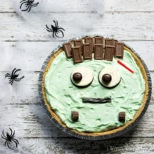 A close up of a light green colored pie with eyeballs, smile and hair made from candy and cookies