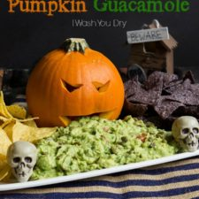 A pumpkin on a tray with a carved face surrounded by chips and a pile of guacamole coming from the pumpkin's mouth and in front of it