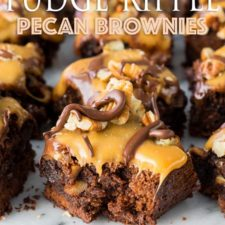 A close up of squares of brownies topped with caramel, chocolate and pecans