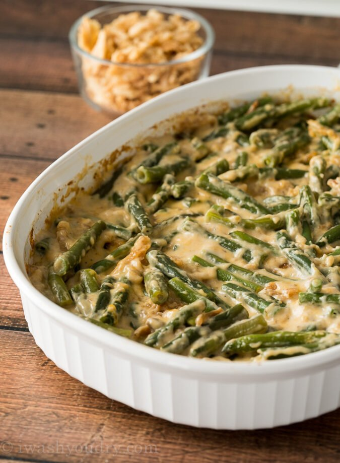 Remove the classic green bean casserole from the oven and stir it up. Top with additional fried onions and pop back into the oven until browned.