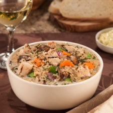 A bowl on a table of Wild Rice Soup with grilled chicken and veggies