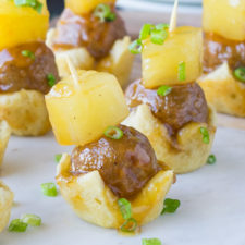 A close up of meatballs on an individual mini crust with a pineapple on top and held together with a toothpick