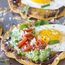 A close up of food, with flat corn tortilla shell with beans, guacamole, fried egg, tomatoes and cheese