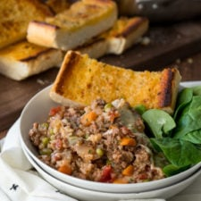 A bowl of food on a table, with Beef, spinach and bread