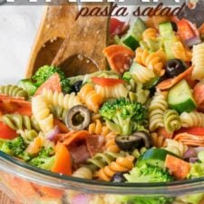 A bowl of pasta salad, with colorful curly pasta, olives, pepperoni, broccoli, cucumbers and tomatoes