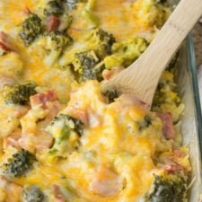 A close up of casserole in a clear glass dish, with rice, ham, broccoli and cheese