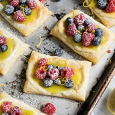 A close up of pastries on a pan topped with a lemon sauce and berries