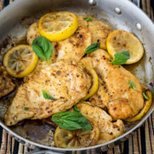 A pan of food with chicken breasts and lemon slices