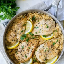 A pan of food, with chicken and lemons