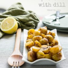 A serving bowl displayed on a table full of Pan Roasted Lemon Potatoes with dill.