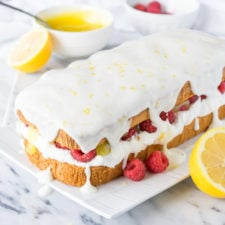 A loaf of pound cake on a plate on a table, with white frosting and an exposed center of lemon raspberry filling