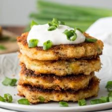 A close up of mashed potato cakes topped with sour cream and chives