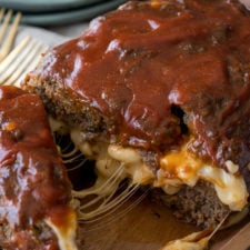 A close up of food, with meatloaf, cheese and sauce