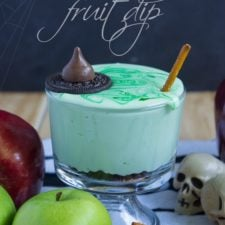 A bowl of green chocolate chip cream cheese fruit dip made to look like a witches potion pot