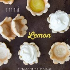 A close up of mini pie crusts, some empty, some with just lemon cream and some topped with whipped cream