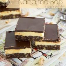 Three Nanaimo bars stylishly stacked on a plate for display