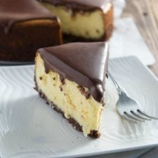 A slice of cheesecake on a plate topped with a chocolate frosting
