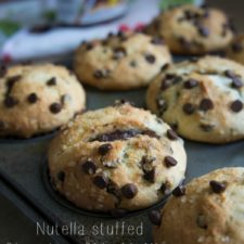 A close ups of a pan of chocolate chip muffins stuffed with Nutella