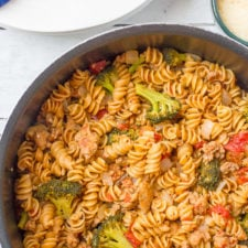 A pot of food, with pasta, sausage, broccoli and other veggies