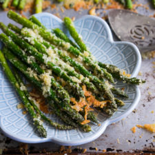 A pile of roasted asparagus displayed on a decorative bowl topped with Parmesan cheese