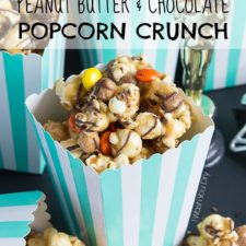 Peanut butter and chocolate popcorn displayed on a table in a white and turquoise stripped container