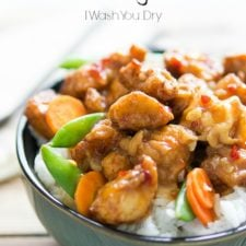 A close up of a bowl of Pei Wei Spicy Chicken with peas and carrots on a bed of white rice