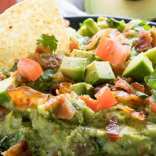 A close up of guacamole with a chip, bacon and tomatoes