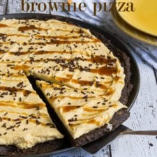 A pumpkin brownie dessert pizza with a slice being removed from it