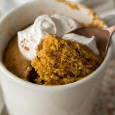 A close up of a mug with pumpkin cake and whipped cream