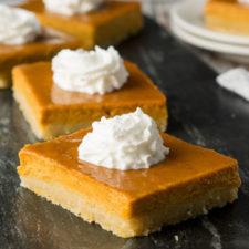 a close up of squares of pumpkin pie, topped with whipped cream