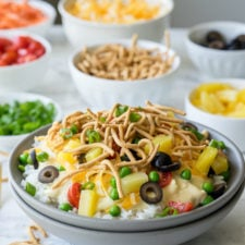 A close up fo a bowl food with rice, chicken sauce, veggies and other toppings