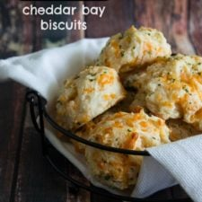 A bowl of cheddar biscuits on a wooden surface