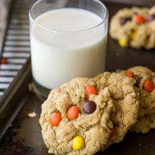 A close up of cookies with Reese's Pieces on them next to a glass of milk