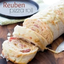 A close up of a log of Reuben Pizza Role with a couple slices cut from it