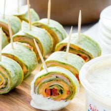 A close up of sliced wraps on a table skewered with a toothpick