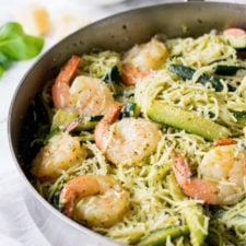 Skillet on a table with shrimp pesto, pasta and veggies