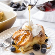 Bread slices on a plate topped with syrup, whipped cream and blueberries