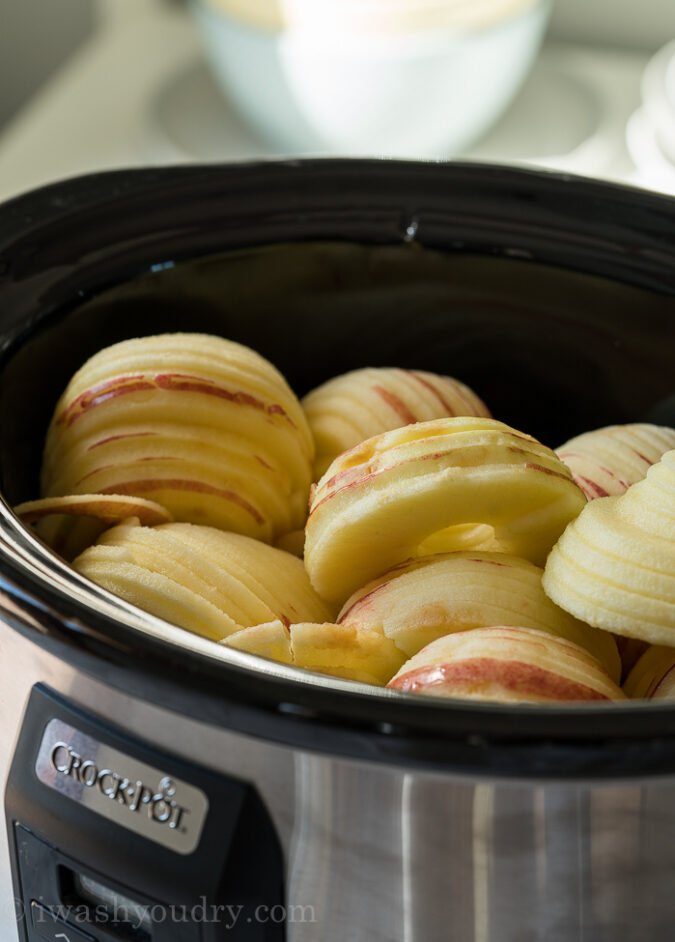 Place the peeled apples into the slow cooker and add water.
