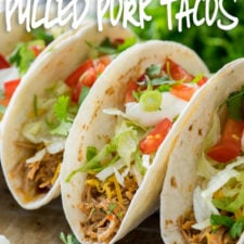 Close up of soft taco shells filled with shredded pork and taco toppings