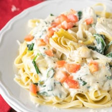 A dish is filled with pasta topped with a white sauce artichokes and veggies.