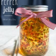A glass mason jar of Sweet Pepper Jelly tied with a red checkered bow