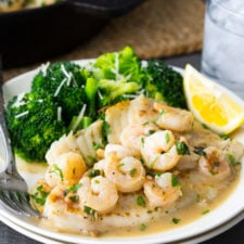 A plate of food on a table, with shrimp, tilapia, broccoli and a slice of lemon